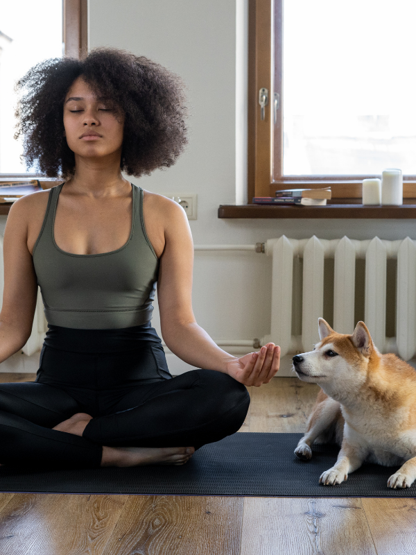 woman doing meditation with dog