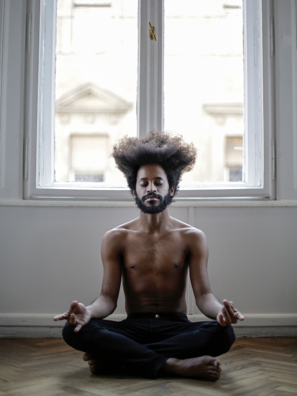 man meditating on apartment floor